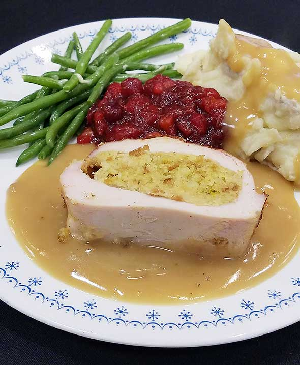 Photo of turkey plate with fresh green beans, mashed potatoes and cranberry sauce.